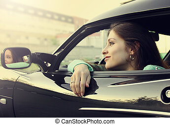 Beautiful smiling girl sitting in new car and looking from...