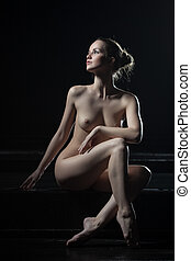 Pretty young woman posing naked in dark - Full length...