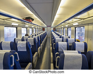 Interior of a passenger train with empty seats -...