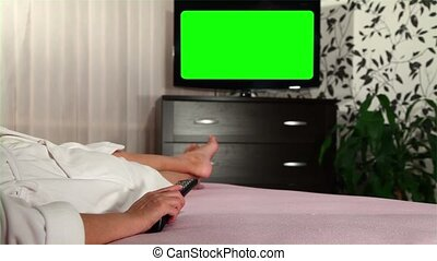 Woman watches green screened TV 2 - Woman watches television...
