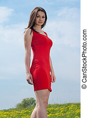 Young pretty woman in red dress against blue sky