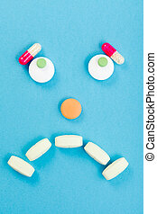 Sad smileyface made of pills - Unhappy drugs on blue...