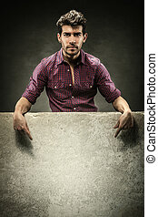Attractive man with banner over grey background
