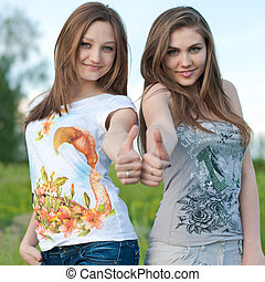 Two happy friends thumbs up - Two happy teenage female...