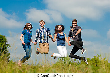 Happy four teenage friends jumping against blue sky