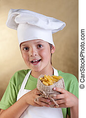 Happy boy with chef hat holding raw pasta in small sack