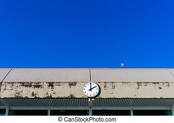 a clock in front of blue sky