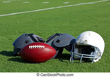 American Football and Helmet on the Field with Shoulder Pads