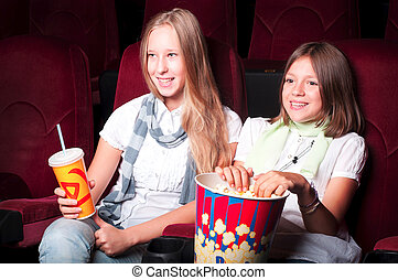 teen girls at the cinema - teen girls in the movie theater,...