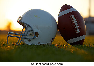 Football and Helmet on the Field at Sunset - American...