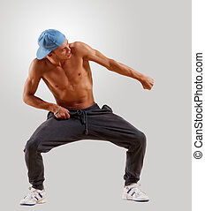 young man dancing hip hop - young man in a blue cap dancing...