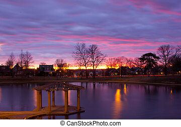 Sunset over gazebo - Sunset over a gazebo and pond in a...
