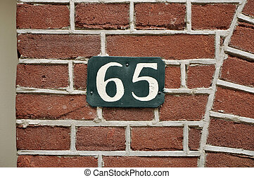 Number Sixty-five - House Number Sixty-five sign on a brick...