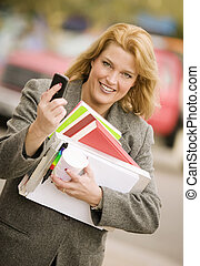 Woman with many books on a sidewalk - Pretty smiling woman...