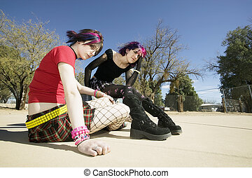 Two Punk Girls Sitting on a cement playground
