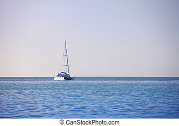 White sailing catamaran on calm sea