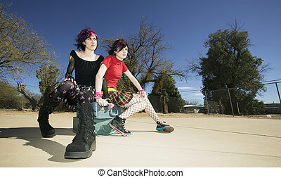 Two Punk Girls Sitting on Suitcases - Two Punk Girls Sitting...