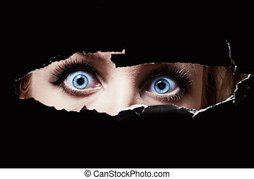 Blue eyes of a young woman peeping through a hole