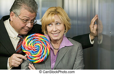 Man in office offers coworker a lollipop - Executive in...