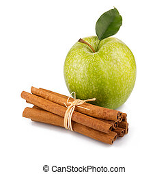 Ripe green apple with cinnamon sticks isolated on white...