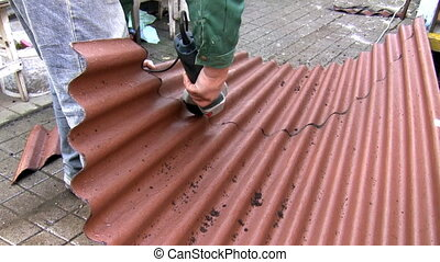 Man cutting roof sheet - Man is cutting plastic roof sheet...