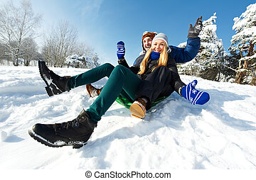 young happy couple sledding in winter - happy young smiling...