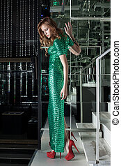 Young woman in green fashion dress walk on stairs