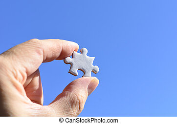 Plain white jigsaw puzzle on Background of blue sky.