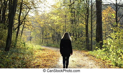 blond woman autumn road - blond woman walk on autumn forest...