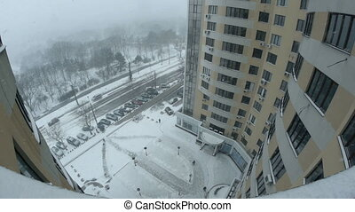 Snowing in the city. View from high-rise building.