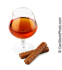 Glass with cognac and chocolate isolated on white