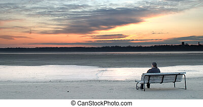 Alone on the beach - Lonely man on a bench at the beach