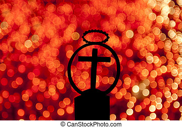 Cross and candles - silhouette of a cross with a blurred red...