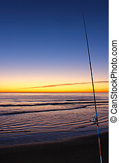 Fishing rod - A fishing rod on a beach at the sunset