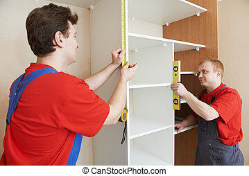 Wardrobe joiners at installation work - Two carpenters...