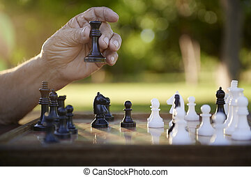 Active retired people, senior man playing chess at park