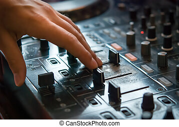 DJ playng on professional mixing controller Small depth of...