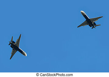 Two flying planes - two flying planes isolated over blue sky