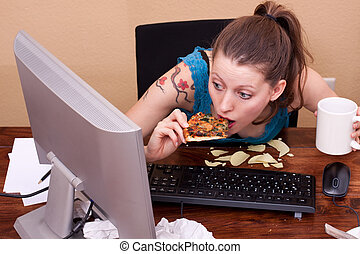 young woman sitting in front of the monitor eats pizza