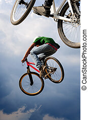 Airborne bikes - Two BMX bikers high up in the air. Some...