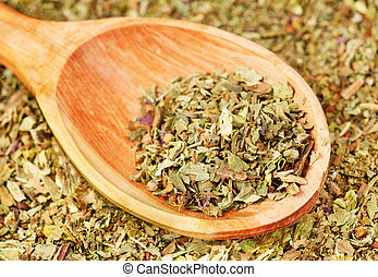 Pile of ground dried Basil (Sweet Basil) as background with wooden spoon. Used as a spice in culinary herb all over the world. The plant is also used in medicine.