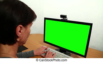 Woman uses a computer Over his sho - Over the shoulder of a...