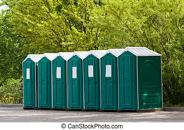 Green plastic toilet booths in park