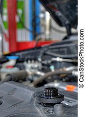 Oil changing - Car servicing mechanic pouring fresh oil to...