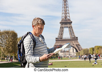 man - the traveler near the Eiffel Tower looks in a map of...