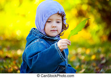 Little girl with green leaves in the hands