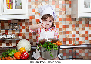 Girl in a cook cap with a ladle in a hand sits on a kitchen table