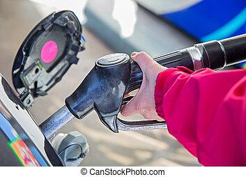 woman pumping gasoline - Woman left hand pumping gasoline...
