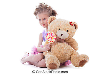 Little girl with lollipop and soft toy. Isolated on white
