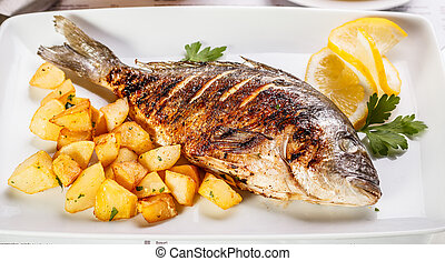Bream fish garnished with potato and lemon